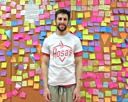 Rosa's Pizza owner Mason Wartman standing in front of the gifted $1 post-it notes (photo credit: Mason Wartman via People.com)